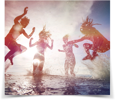 Young people dancing in the water with sunlight in the background